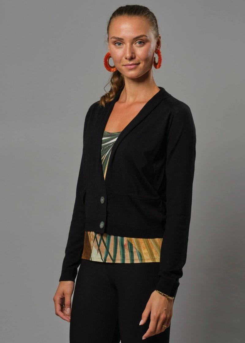 Connemara kurze Strickjacke Damen schwarz. Eine Merino Jacke Damen die perfekt über ein Kleid passt, mit großen Perlmuttknöpfen.